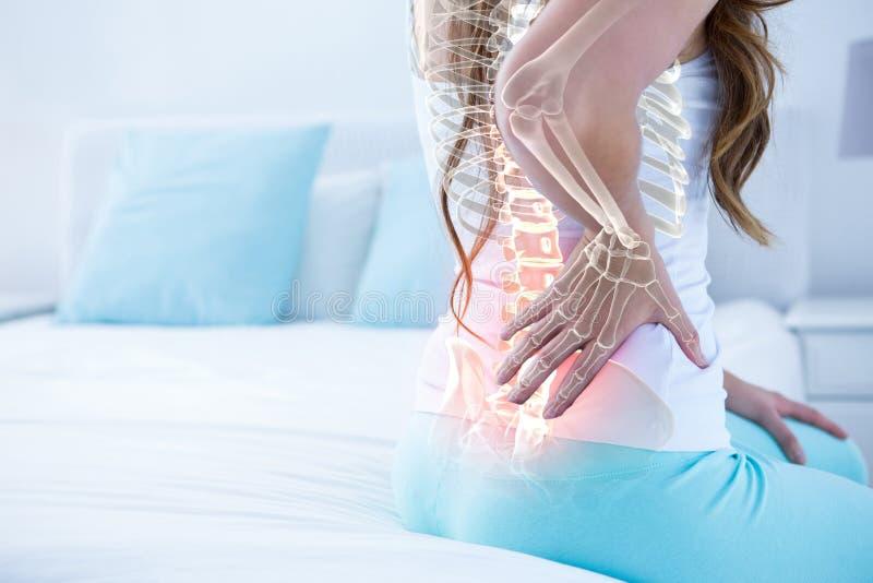 Ψηφιακό σύνθετο της τονισμένης σπονδυλικής στήλης της γυναίκας με τον πόνο στην πλάτη στοκ εικόνα