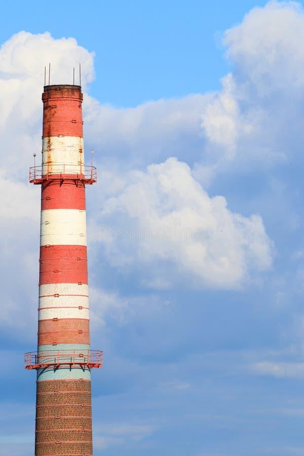 Ψηλός κόκκινος και άσπρος σωλήνας καπνοδόχων των σύγχρονων εγκαταστάσεων και του μπλε ουρανού στοκ εικόνες