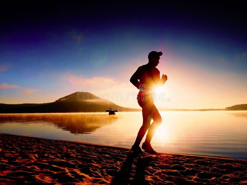 Ψηλό κατάλληλο άτομο που τρέχει κατά μήκος της ακροθαλασσιάς το πρωί Υγιές αρσενικό στην παραλία στοκ φωτογραφίες