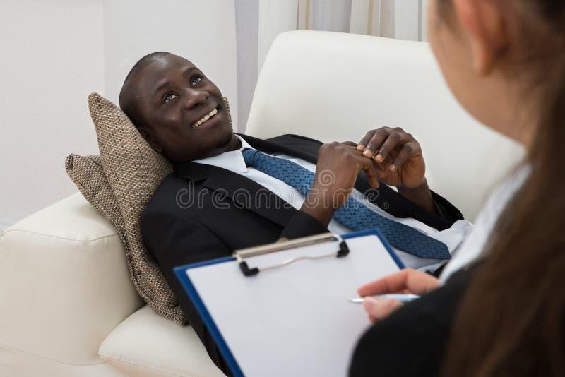 Ψυχίατρος που κάνει τις σημειώσεις μπροστά από τον ασθενή στοκ εικόνα με δικαίωμα ελεύθερης χρήσης