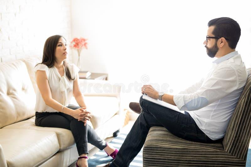 Ψυχολόγος που ακούει τη γυναίκα που μιλά για τα προβλήματά της στοκ εικόνες