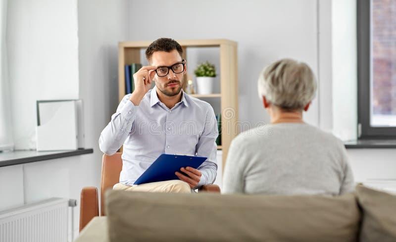 Ψυχολόγος που ακούει τον ανώτερο ασθενή γυναικών στοκ εικόνα με δικαίωμα ελεύθερης χρήσης