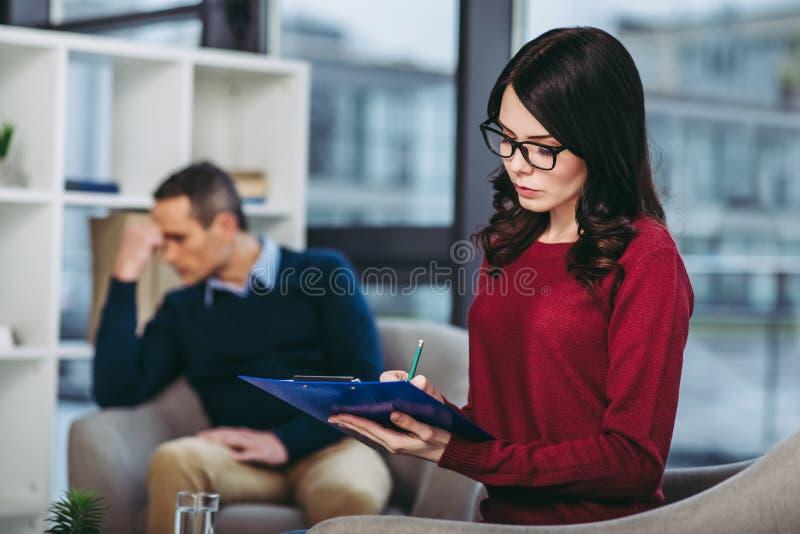 Ψυχολόγος που κάνει τις σημειώσεις στο έγγραφο στοκ εικόνα με δικαίωμα ελεύθερης χρήσης