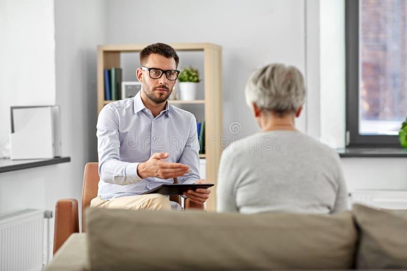 Ψυχολόγος που μιλά στον ανώτερο ασθενή γυναικών στοκ εικόνες