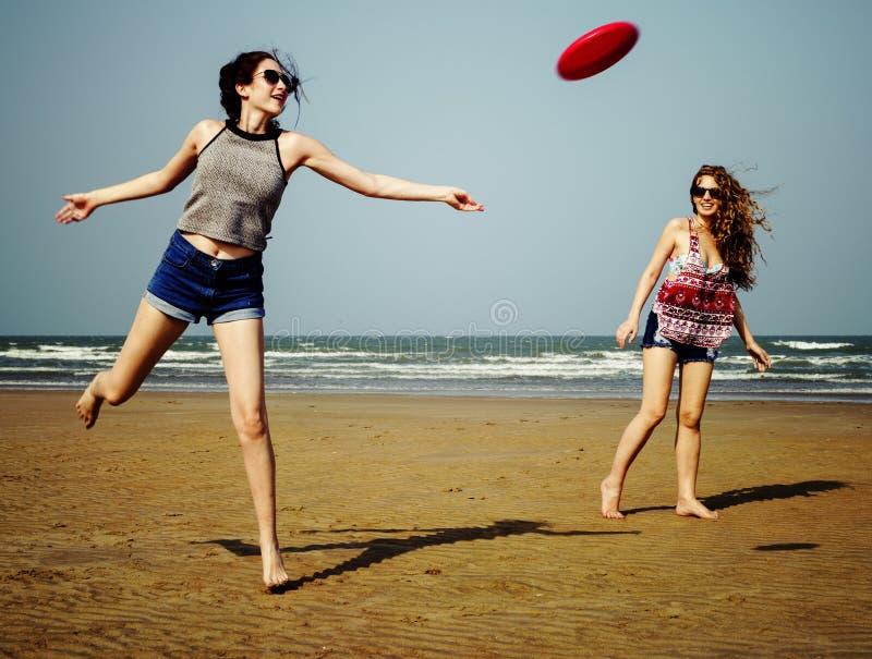 Ψυχρή έννοια θερινών θηλυκή κοριτσιών ακτών παραλιών Frisbee στοκ φωτογραφία με δικαίωμα ελεύθερης χρήσης