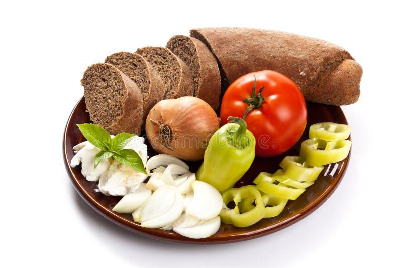 Ψωμί και φρέσκα λαχανικά στο πιάτο που απομονώνεται στην ξύλινη πλάτη στοκ εικόνες