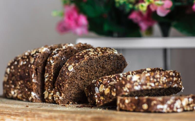 Ψωμί σίκαλης με τους τεμαχισμένους σπόρους †‹â€ ‹ Τεμαχισμένο μαύρο ψωμί â€ ‹â€ ‹στην παλαιά ξύλινη σανίδα στο υπόβαθρο του ντε στοκ φωτογραφία