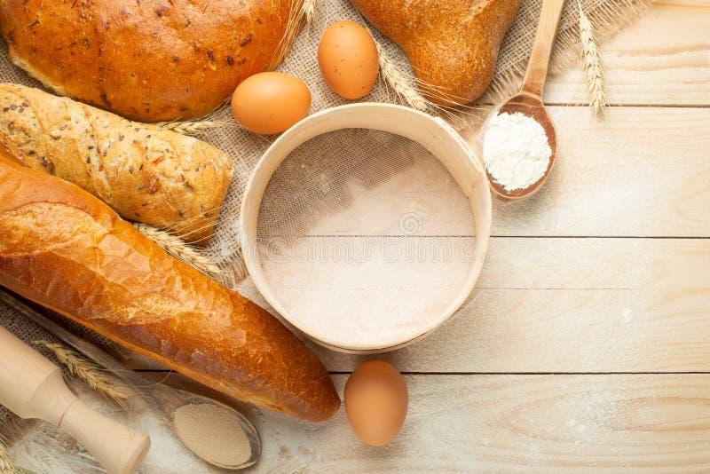 Ψωμί των διαφορετικών ποικιλιών σε ένα ξύλινο υπόβαθρο με το διαστημικό υπόβαθρο αντιγράφων Η έννοια του αρτοποιείου, του μαγειρέ στοκ εικόνες