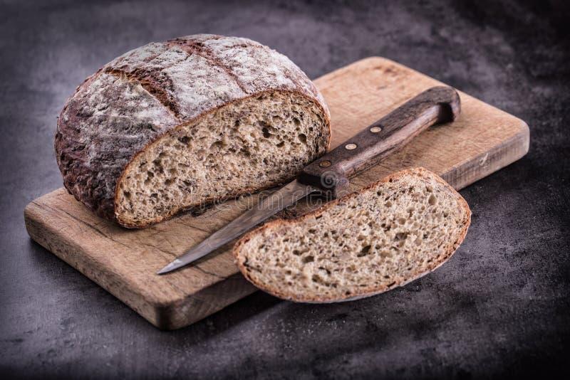 Ψωμί ψωμί φρέσκο σπιτικός παραδοσιακός ψ&ome Το τεμαχισμένο ψωμί σκορπίζει το μαχαίρι και το κύμινο στοκ εικόνες