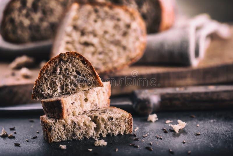 Ψωμί ψωμί φρέσκο σπιτικός παραδοσιακός ψ&ome Το τεμαχισμένο ψωμί σκορπίζει το μαχαίρι και το κύμινο στοκ εικόνα