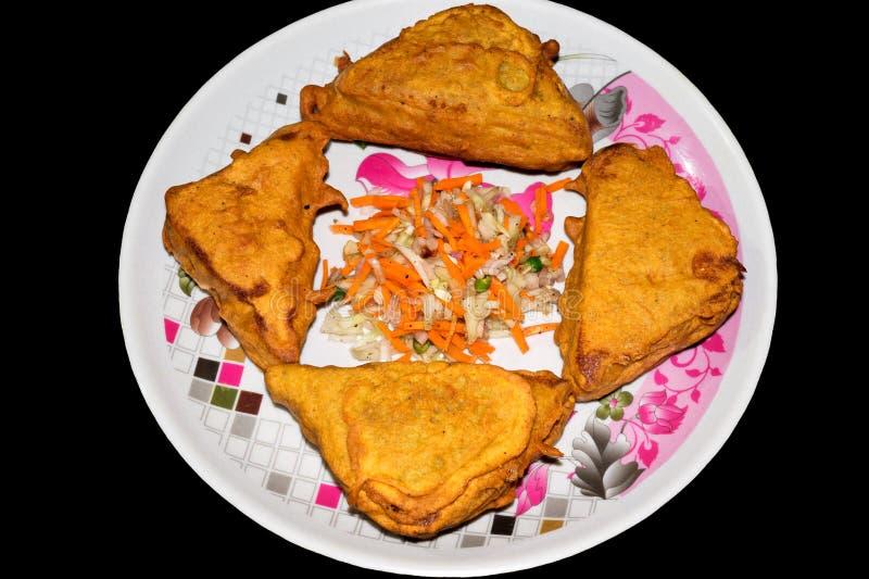 Ψωμί Pakora μορφής τριγώνων σε ένα πιάτο στο μαύρο υπόβαθρο με την τεμαχισμένη σαλάτα στοκ φωτογραφία με δικαίωμα ελεύθερης χρήσης