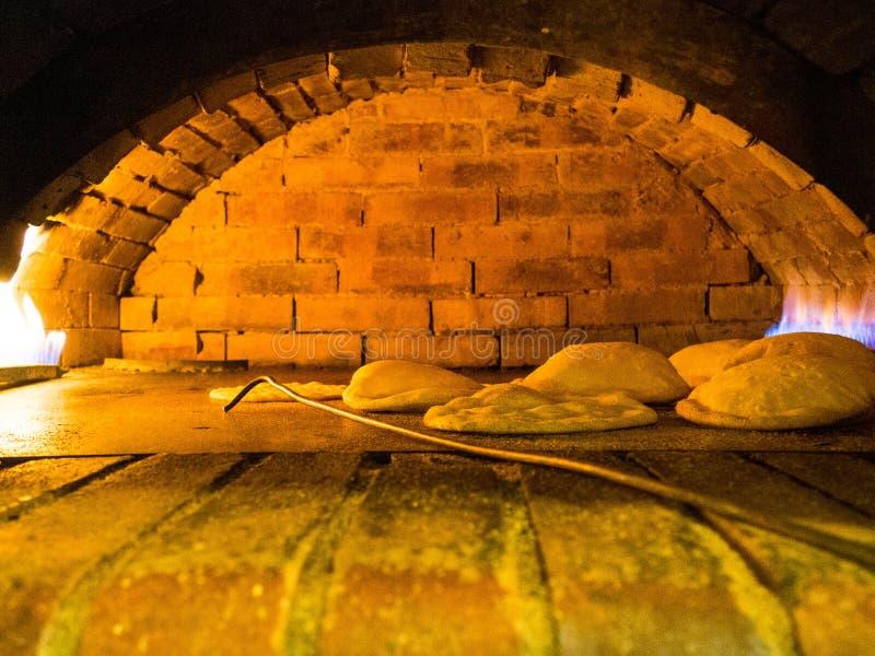 Ψωμιά Pita στο χαρακτηριστικό τούβλο, λιβανέζικο ψωμί σε έναν φούρνο αρτ στοκ φωτογραφία
