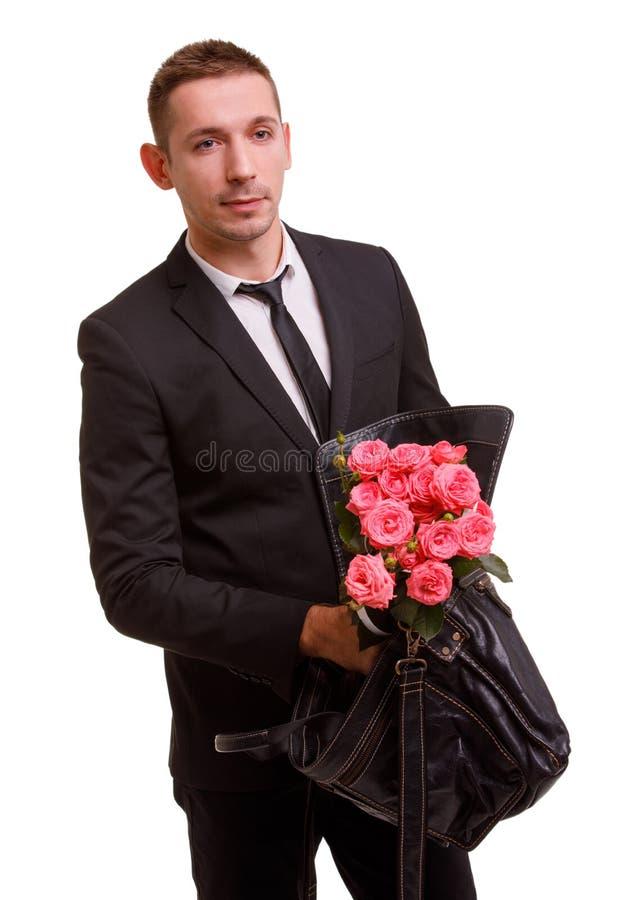 Ωθήσεις τύπων μια ανθοδέσμη σε μια τσάντα και βλέμματα στην πλευρά σε ένα απομονωμένο λευκό υπόβαθρο στοκ εικόνα