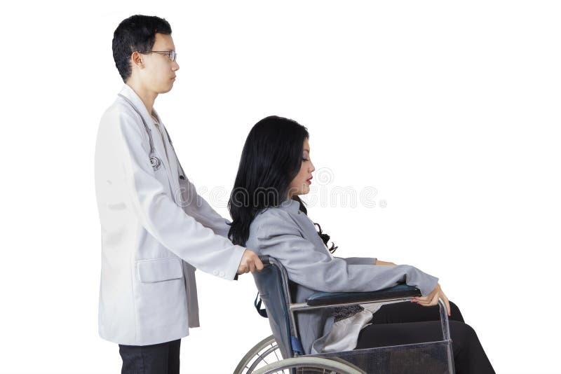 Ωθώντας αναπηρική καρέκλα γιατρών με το με ειδικές ανάγκες ασθενή στοκ φωτογραφία με δικαίωμα ελεύθερης χρήσης