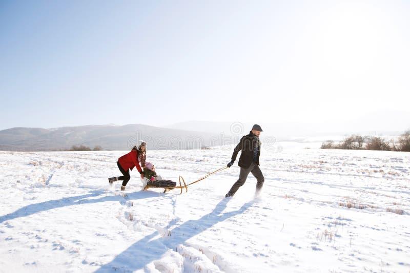 Ωθώντας κόρη μητέρων στο έλκηθρο, πατέρας που τραβά την Χειμερινό NA στοκ φωτογραφίες