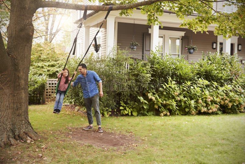 Ωθώντας κόρη πατέρων στην ταλάντευση κήπων στο σπίτι στοκ φωτογραφίες με δικαίωμα ελεύθερης χρήσης