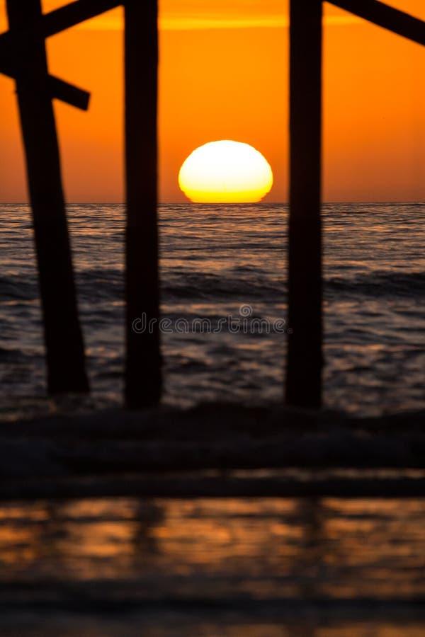 Ωκεάνια σκιαγραφία αποβαθρών κατά τη διάρκεια της πορτοκαλιάς δυτικής ακτής ηλιοβασιλέματος στοκ φωτογραφία
