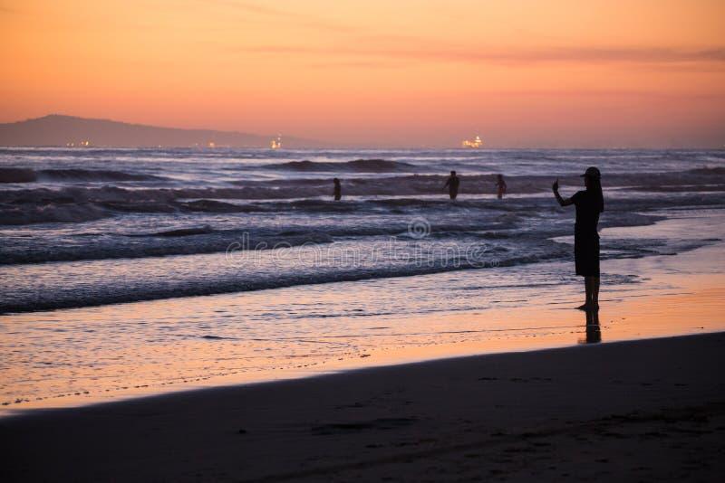 Ωκεάνιες σκιαγραφίες παραλιών κατά τη διάρκεια της πορτοκαλιάς δυτικής ακτής ηλιοβασιλέματος στοκ φωτογραφίες