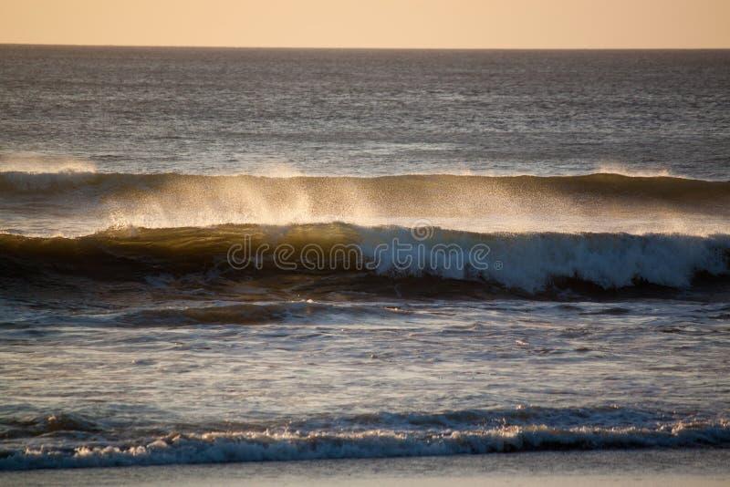 Ωκεάνιος ψεκασμός από τα κύματα στο ηλιοβασίλεμα στοκ εικόνες