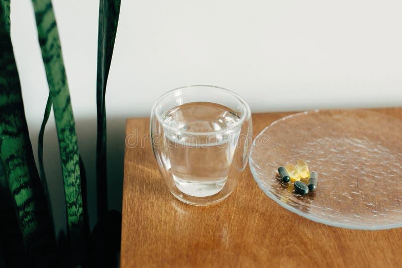 Ωμέγα 3, σπιρουλίνα, καψάκια χλωροφύλλης και ποτήρι νερό σε ξύλινο τραπέζι Συμπληρώματα διατροφής, βιολογικά δραστικά πρόσθετα στοκ εικόνα
