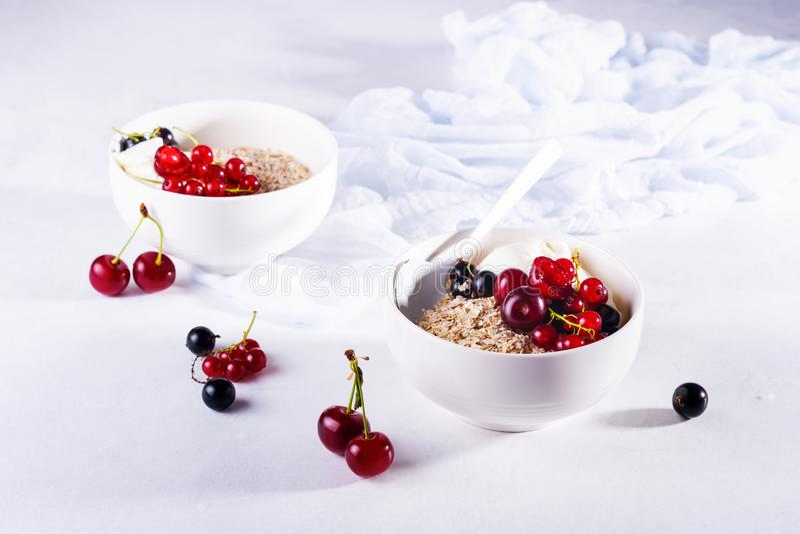 Ωμό αλεύρι βρώμης για την παρασκευή υγιούς πρωινού σε λευκό κεραμικό μπολ σε ανοιχτό φόντο στοκ εικόνες με δικαίωμα ελεύθερης χρήσης