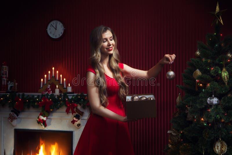 ωραία γυναίκα με κόκκινο φόρεμα κοντά στο χριστουγεννιάτικο δέντρο στοκ φωτογραφίες