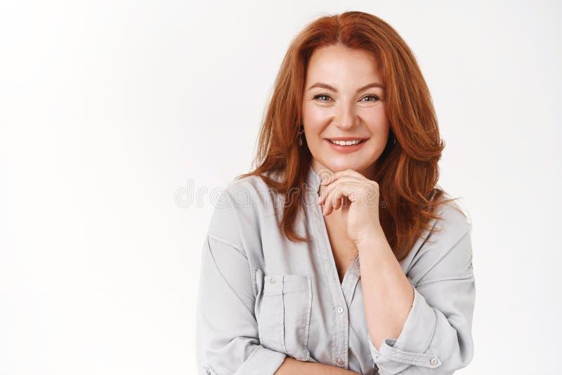 Ωραία όμορφη, ειλικρινής κοκκινομάλλα, ώριμη γυναίκα που ακούει περιέργως χαμογελαστή, ευχαριστημένη με τη συζήτηση κρατήστε το π στοκ εικόνα με δικαίωμα ελεύθερης χρήσης