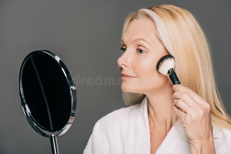 ωριμάστε να κάνει γυναικών makeup εξετάζοντας τον καθρέφτη στοκ φωτογραφίες με δικαίωμα ελεύθερης χρήσης