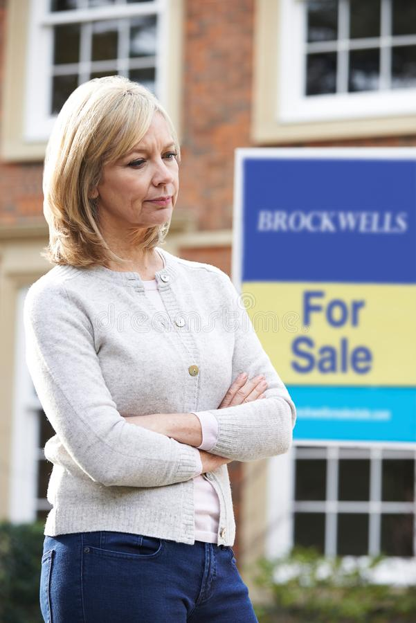Ωριμάστε τη γυναίκα που αναγκάζεται να πωλήσει το σπίτι μέσω των οικονομικών προβλημάτων στοκ εικόνα