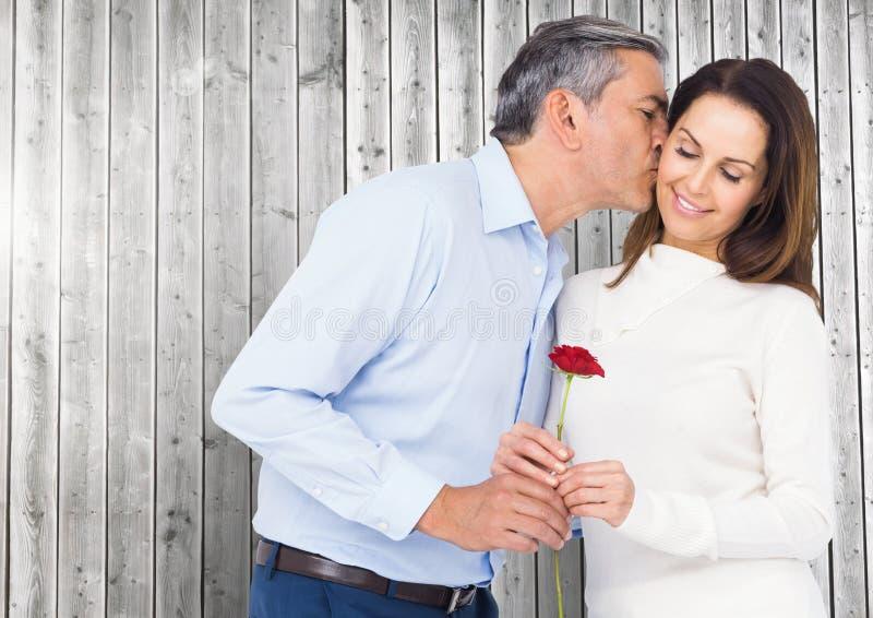 Ωριμάστε τον άνδρα που φιλά δίνοντας ένα κόκκινο ανήλθε στη γυναίκα στοκ φωτογραφία