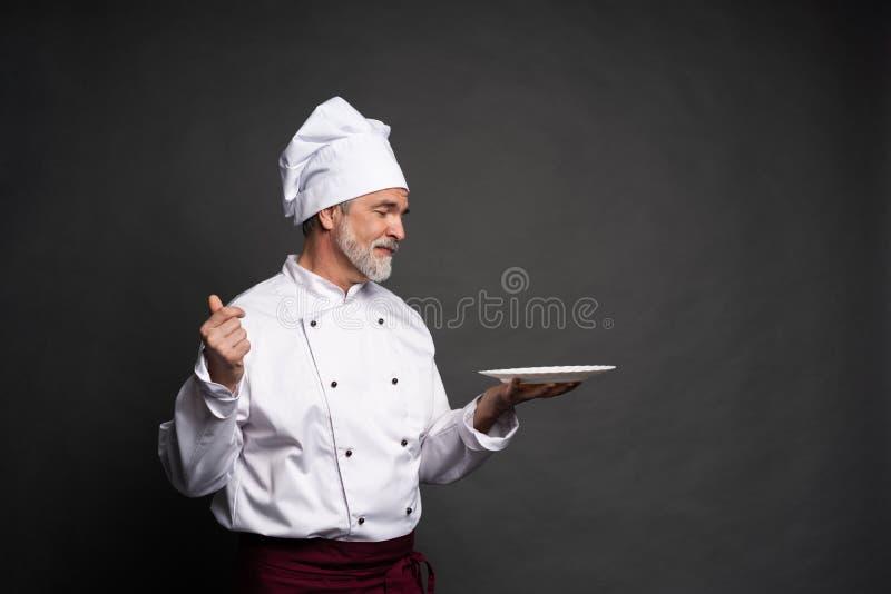 Ωριμάστε τον αρχιμάγειρα μαγείρων που κρατά ένα κενό πιάτο σε ένα μαύρο υπόβαθρο στοκ εικόνες με δικαίωμα ελεύθερης χρήσης