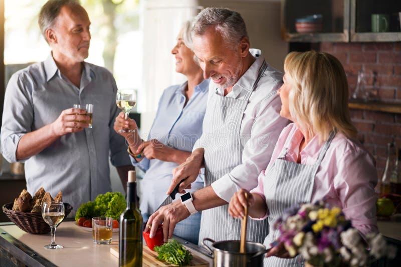 Ωριμάστε τους φίλους που έχουν τη διασκέδαση κάνοντας το γεύμα στοκ εικόνα