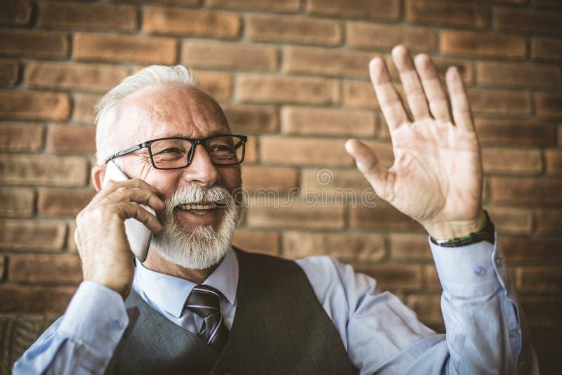 Ωριμάστε το άτομο που κυματίζει μιλώντας στο κινητό τηλέφωνο στοκ εικόνα με δικαίωμα ελεύθερης χρήσης