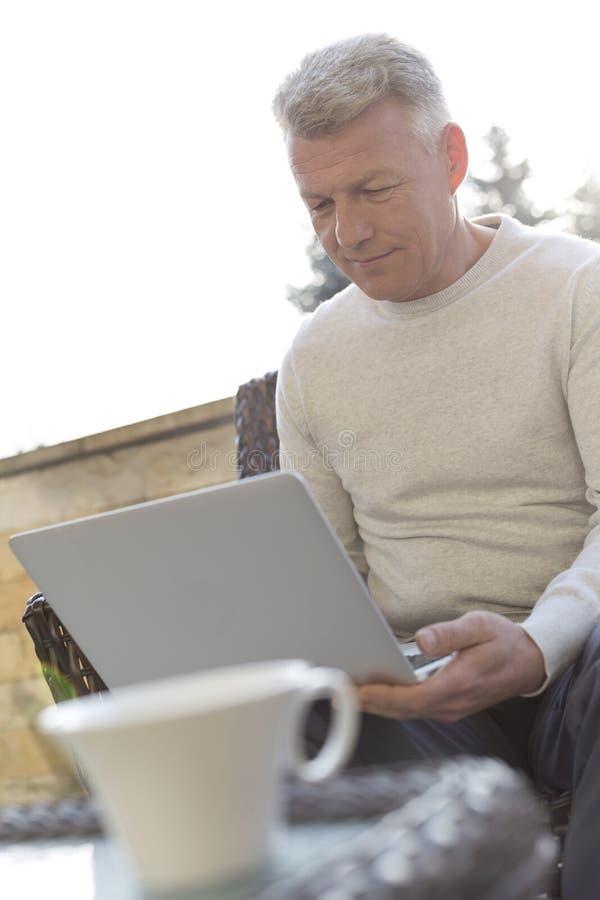 Ωριμάστε το άτομο χρησιμοποιώντας το lap-top καθμένος στο patio στοκ εικόνες