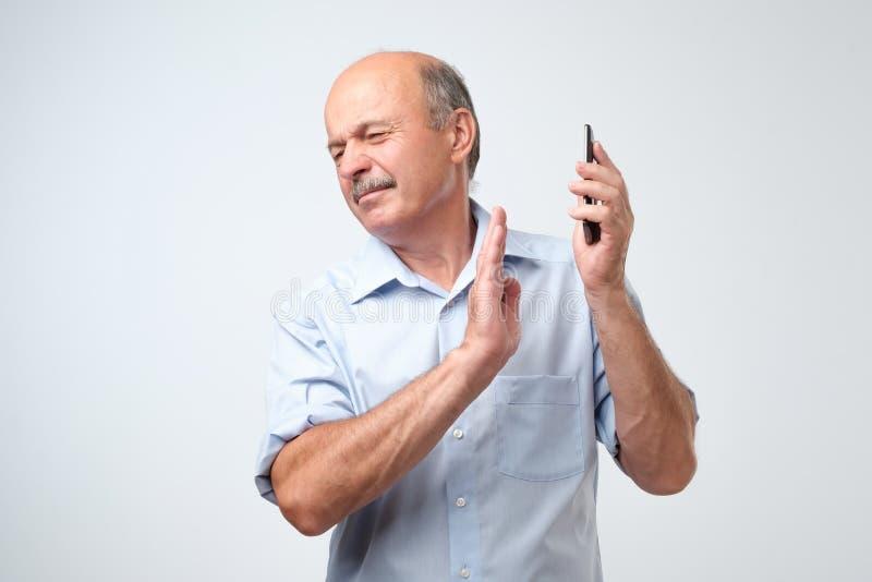 Ωριμάστε το όμορφο άτομο που αρνείται να μιλήσει στο τηλέφωνο πέρα από το υπόβαθρο που γυρίζει το πρόσωπό του από το στοκ εικόνες με δικαίωμα ελεύθερης χρήσης