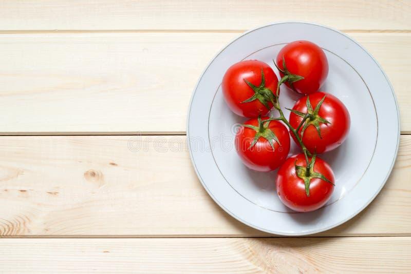 Ωριμασμένες ντομάτες στο άσπρο πιάτο στον ελαφρύ ξύλινο πίνακα με το διάστημα αντιγράφων στοκ εικόνες με δικαίωμα ελεύθερης χρήσης