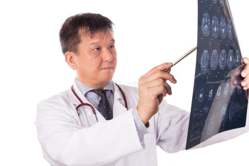 Ωριμασμένος ασιατικός ιατρός νευρολογίας που εξετάζει τις επικεφαλής εικόνες MRI στοκ φωτογραφία