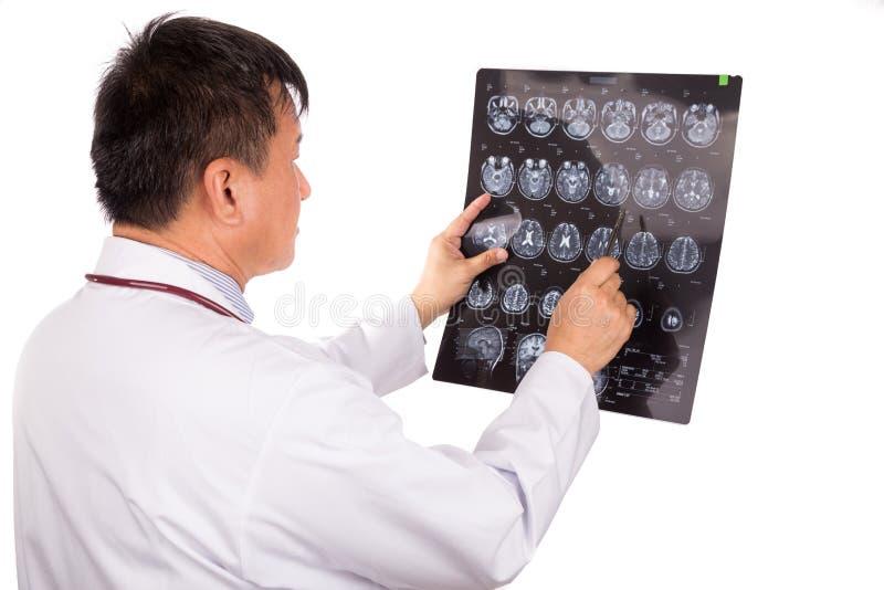 Ωριμασμένος ασιατικός ιατρός νευρολογίας που εξετάζει τις επικεφαλής εικόνες MRI στοκ φωτογραφία με δικαίωμα ελεύθερης χρήσης