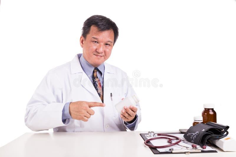 Ωριμασμένος ασιατικός ιατρός που δείχνει στο μπουκάλι ιατρικής στοκ φωτογραφία με δικαίωμα ελεύθερης χρήσης