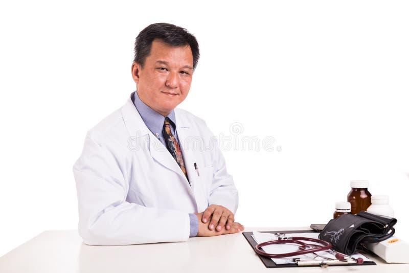 Ωριμασμένος ασιατικός ιατρός που κάθεται πίσω από το γραφείο στοκ εικόνες