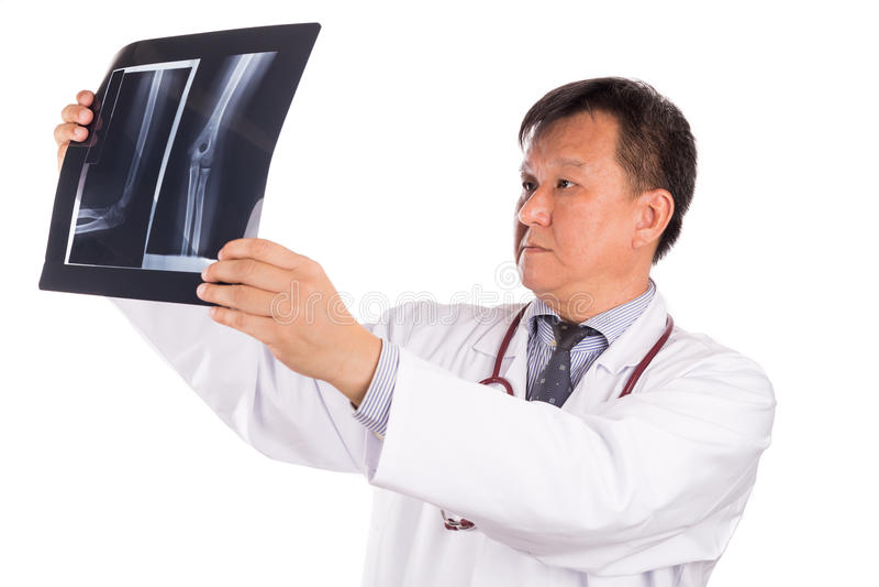 Ωριμασμένος ασιατικός ορθοπεδικός ιατρός που εξετάζει την ταινία ακτίνας X στοκ φωτογραφία με δικαίωμα ελεύθερης χρήσης