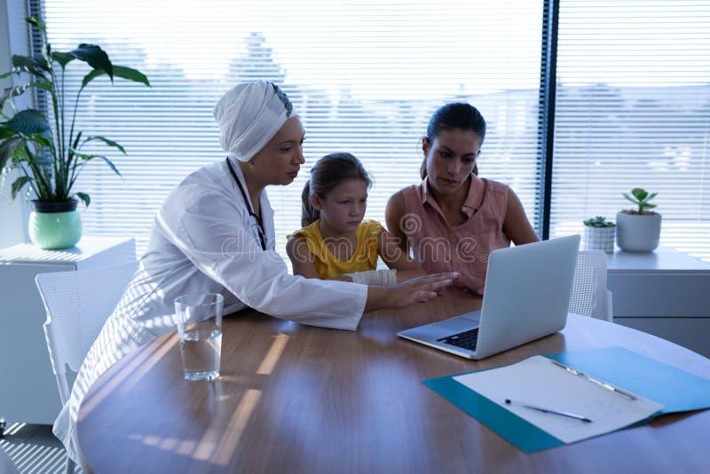 Ωριμασμένος θηλυκός γιατρός που συζητά πέρα από το lap-top με τον ασθενή στην κλινική στοκ εικόνα