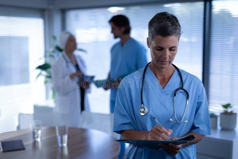 Ωριμασμένος θηλυκός χειρούργος που γράφει στην ιατρική έκθεση στην κλινική στο νοσοκομείο στοκ εικόνα