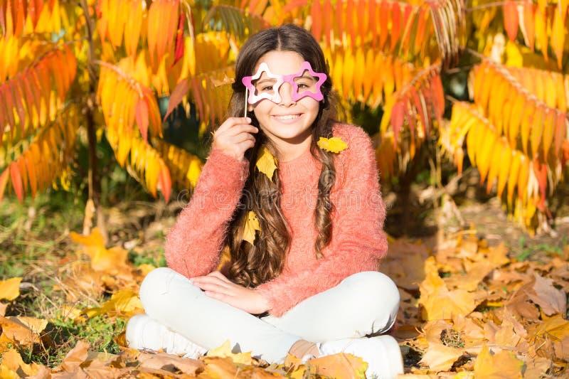 Όλοι του μια μεταμφίεση Πλαστά γυαλιά λίγης λαβής παιδιών στο πρόσωπο Το παιδί κοριτσιών έχει τη διασκέδαση την ημέρα φθινοπώρου  στοκ εικόνες