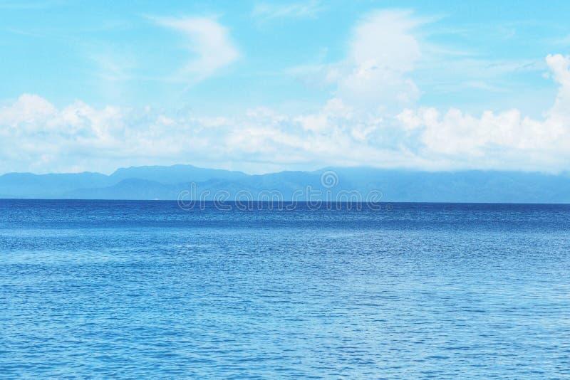 Όμορφα άσπρα σύννεφα στο μπλε ουρανό πέρα από την ήρεμη θάλασσα με την αντανάκλαση φωτός του ήλιου, τον ηλιόλουστο ουρανό και τον στοκ εικόνα
