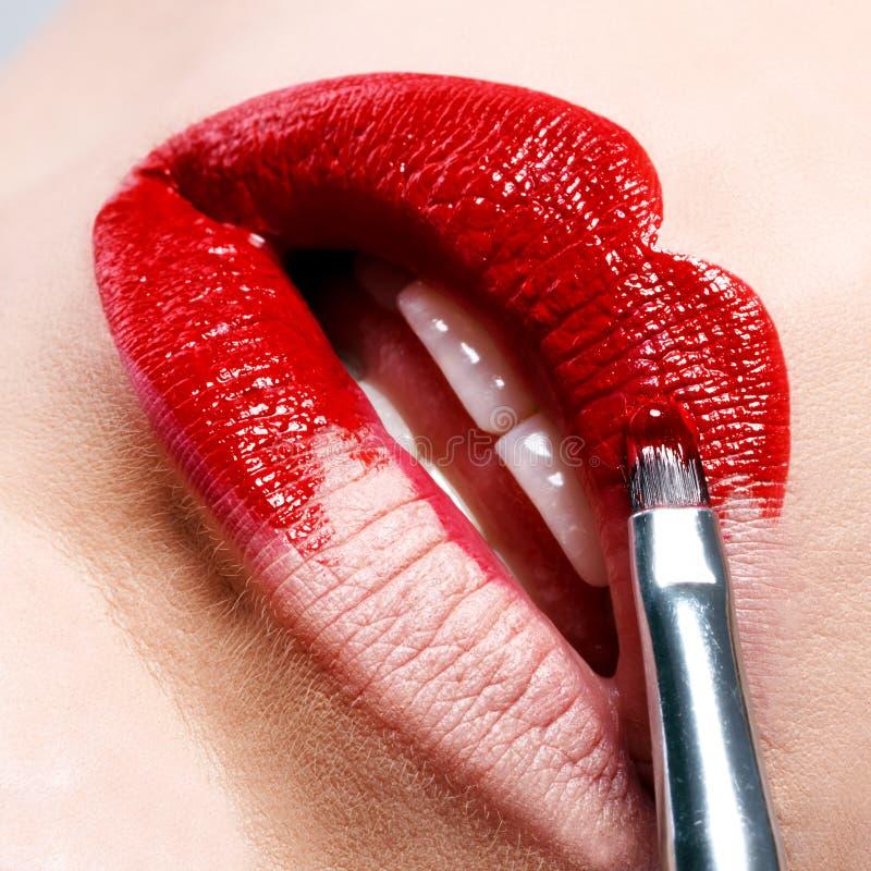 Όμορφα λαμπρά κόκκινα χείλια δεδομένου ότι χρωματίζετε τη βούρτσα στοκ εικόνες