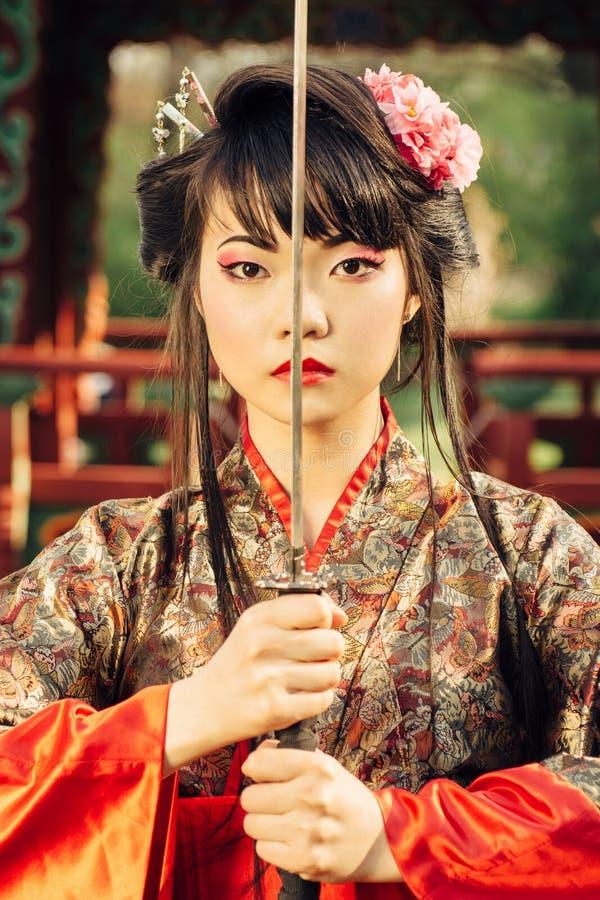 Όμορφα γκέισα στο κιμονό με το ξίφος Σαμουράι στοκ εικόνες