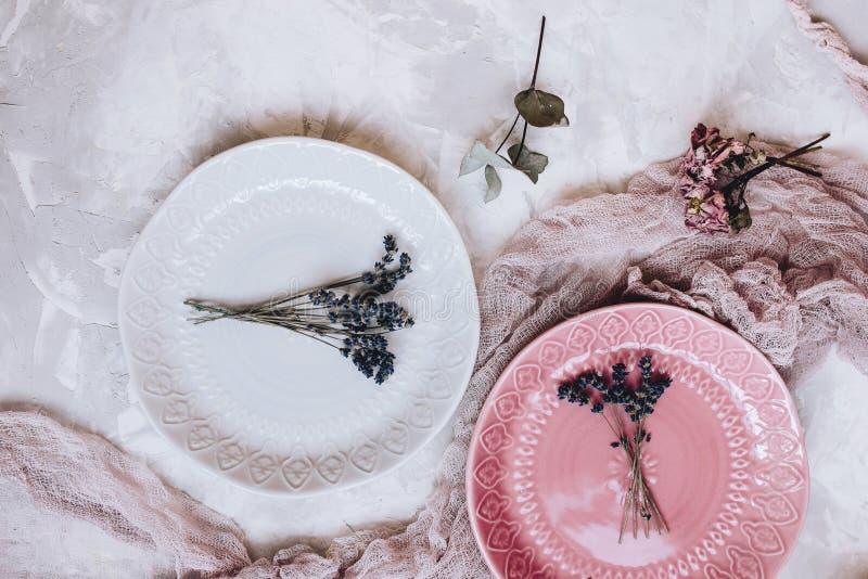 Όμορφα γκρίζα και ρόδινα κεραμικά πιάτα με μια ανθοδέσμη lavender, ρόδινη γάζα στο γκρίζο συγκεκριμένο υπόβαθρο στοκ φωτογραφίες με δικαίωμα ελεύθερης χρήσης