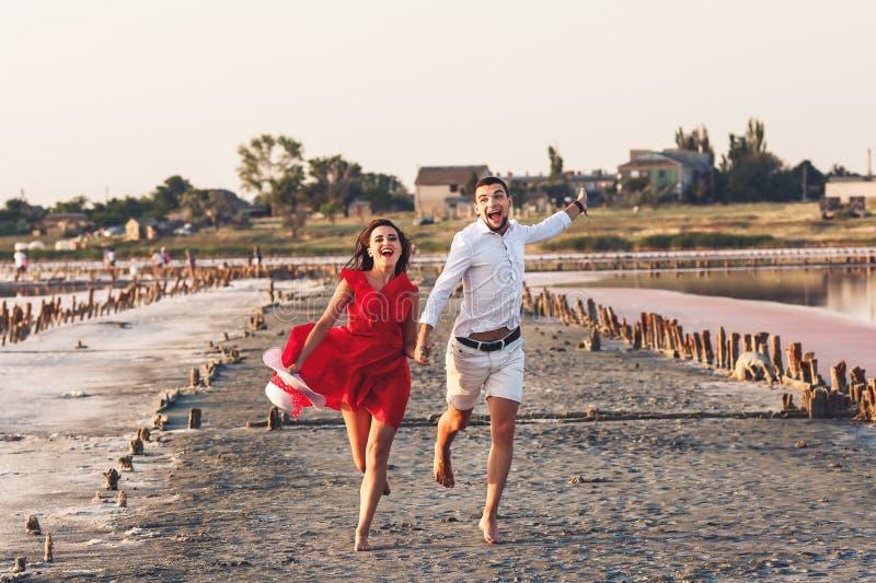 Όμορφα ερωτευμένα αστεία τρεξίματα ζευγών πέρα από μια αλατισμένη λίμνη στοκ φωτογραφία με δικαίωμα ελεύθερης χρήσης