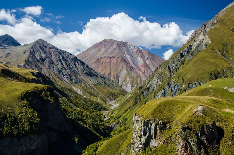 Όμορφα ζωηρόχρωμα βουνά που αντιμετωπίζονται από το μνημείο φιλίας της Ρωσίας Γεωργία σε Kazbegi, Γεωργία στοκ φωτογραφίες